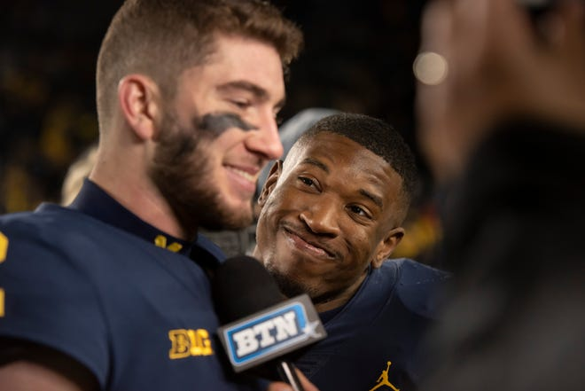 Michigan running back Karan Higdon, right, tries to get teammate quarterback Shea Patterson to laugh while Patterson was being interviewed on live television after Saturday's win over Penn State.