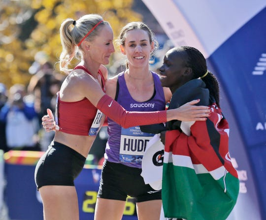 First-place finisher Mary Keitany of Kenya, right, greets American runners Shalane Flanagan, left, and Molly Huddle at the finish line of the New York City Marathon in New York, Sunday, Nov. 4, 2018.