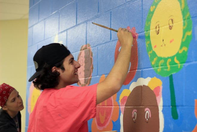 A volunteer paints a mural at Bond Elementary School as a part of The Little Event.