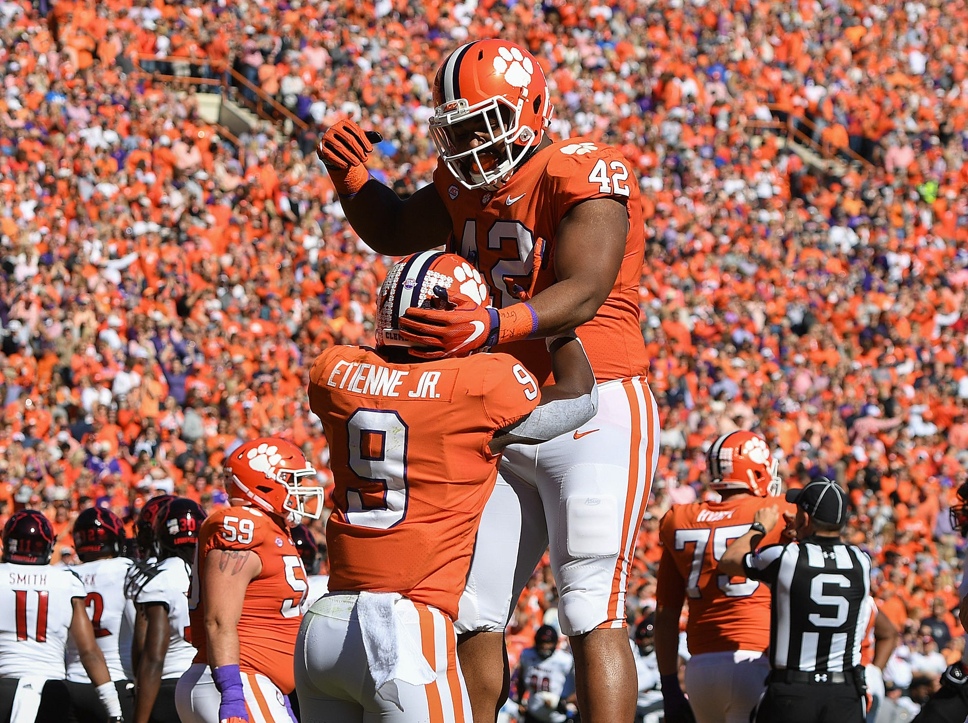 Clemson running back Travis Etienne (9) celebrates with defensive lineman Christian Wilkins (42) after scoring against Louisville during the 1st quarter Saturday, November 3, 2018 at Clemson's Memorial Stadium.