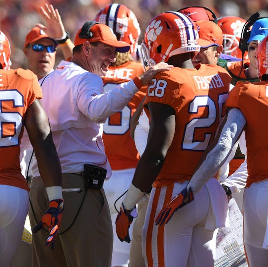 Clemson head coach Dabo Swinney congratulates running back Tavien Feaster (28) after he scored against Louisville during the 1st quarter Saturday, November 3, 2018 at Clemson's Memorial Stadium.