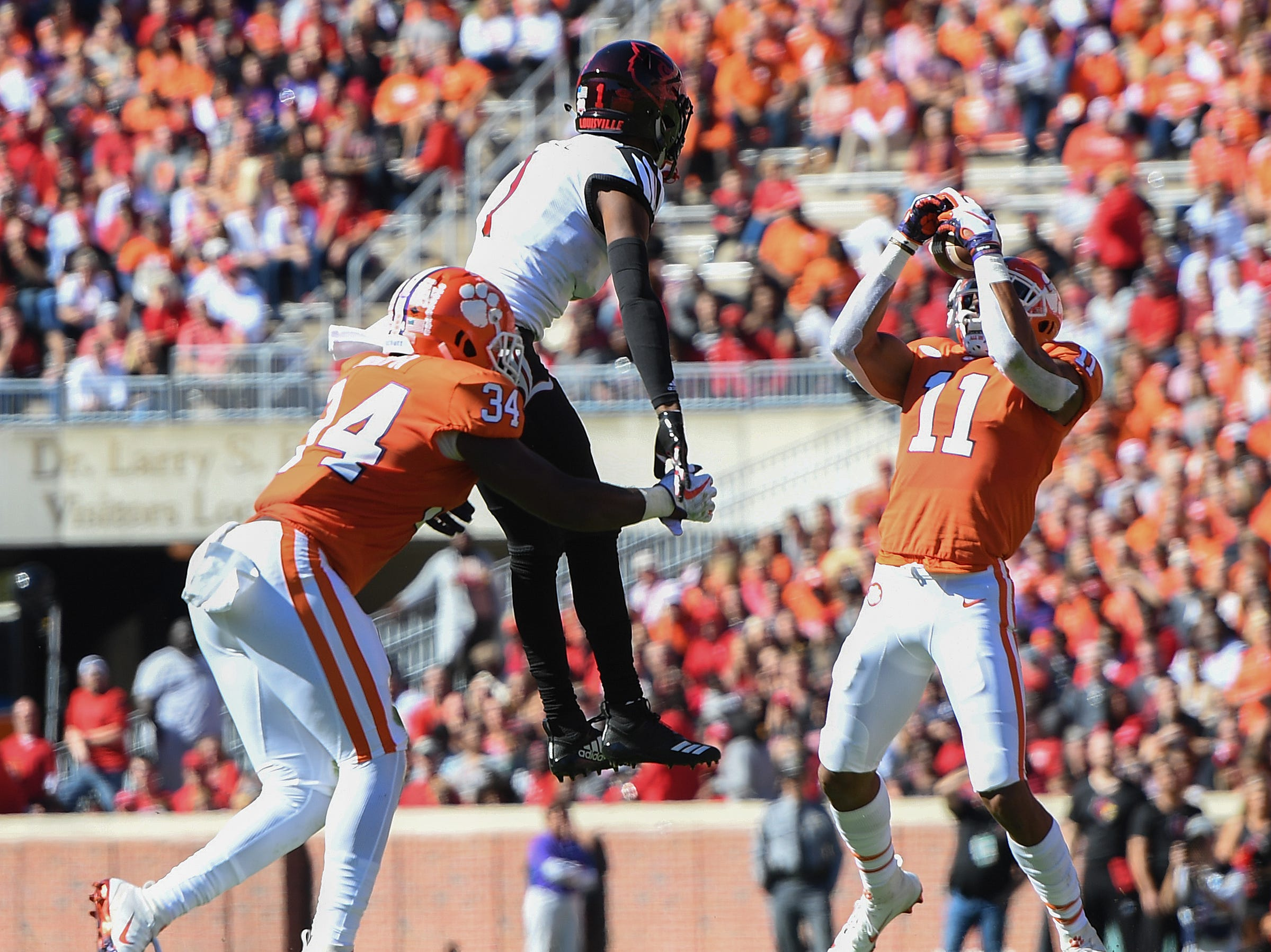 Clemson safety Isaiah Simmons (11) intercepts a pass intended for Louisville wide receiver Chatarius Atwell (1) during the 2nd quarter Saturday, November 3, 2018 at Clemson's Memorial Stadium.