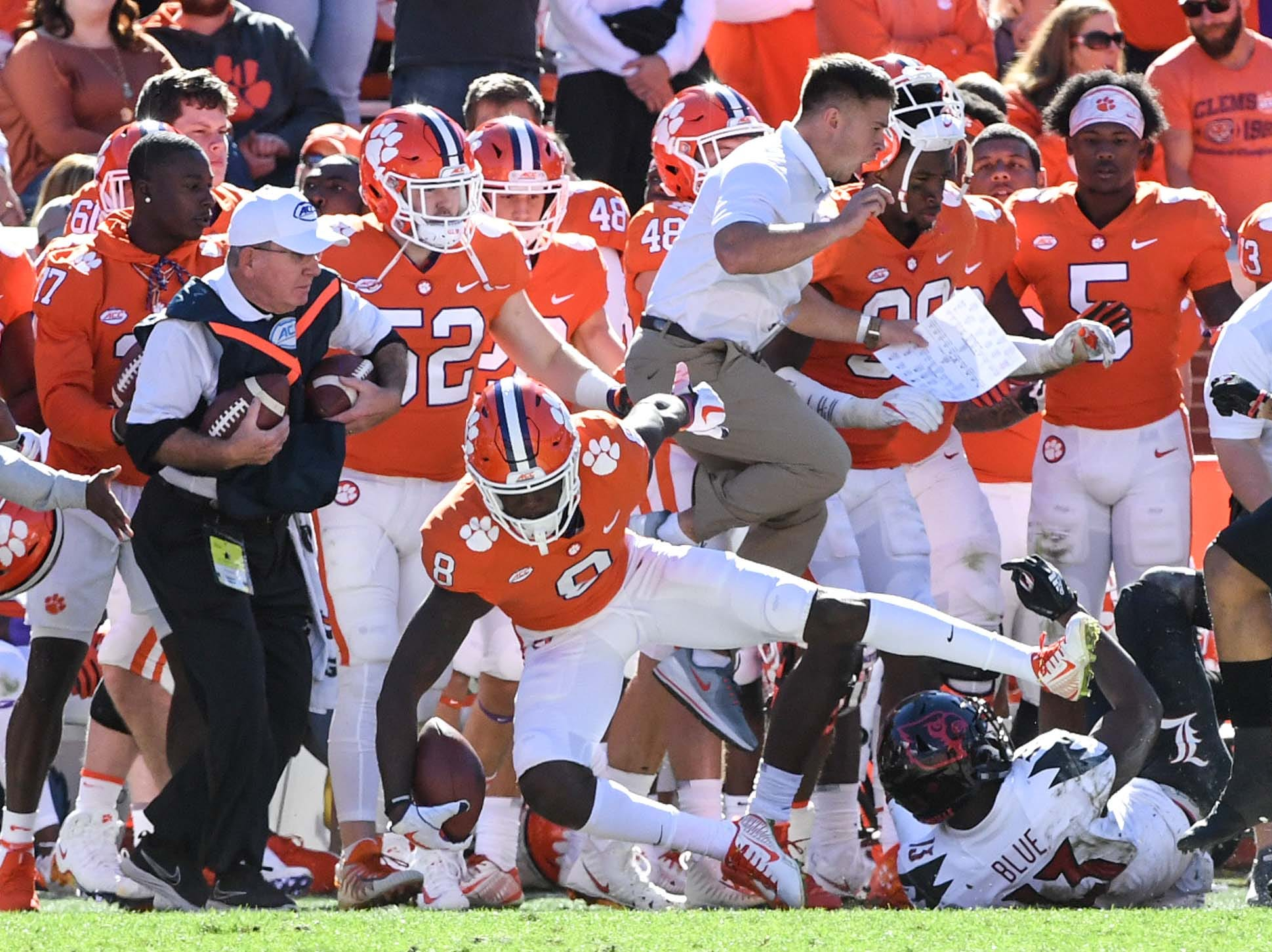 A Clemson assistant leaps out of the way of Clemson wide receiver Justyn Ross (8) going out of bounds near a sideline chain crew worker during the third quarter in Memorial Stadium on Saturday, November 3, 2018.