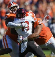 Clemson defensive lineman Clelin Ferrell (99) and defensive lineman Dexter Lawrence (90) bring down Louisville running back Hassan Hall (19) during the 1st quarter Saturday, November 3, 2018 at Clemson's Memorial Stadium.