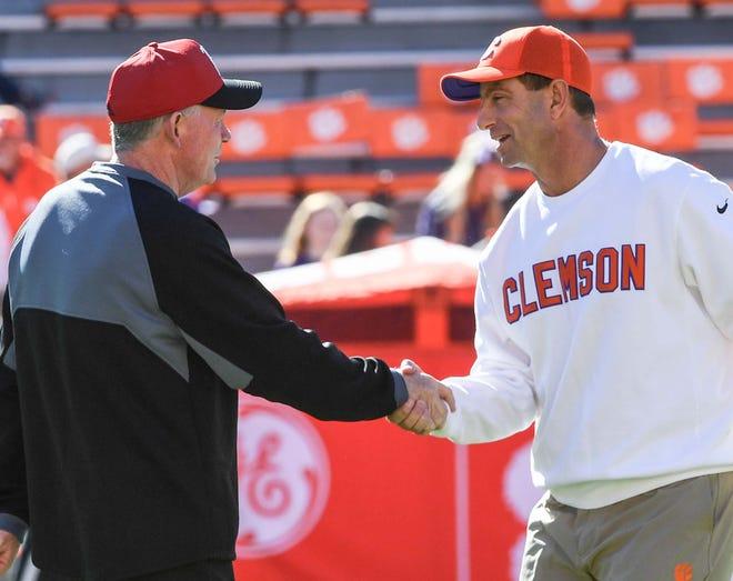 Louisville Head Coach Bobby Petrino, left, shakes hands with Clemson Head Coach Dabo Swinney before the game in Memorial Stadium on Saturday, November 3, 2018.