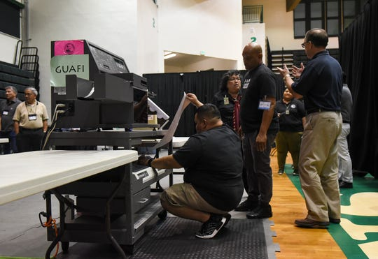 Guam Election Commission workers gather around a tabulating machine during a test election at the University of Guam Calvo Field House, Nov. 4, 2018.