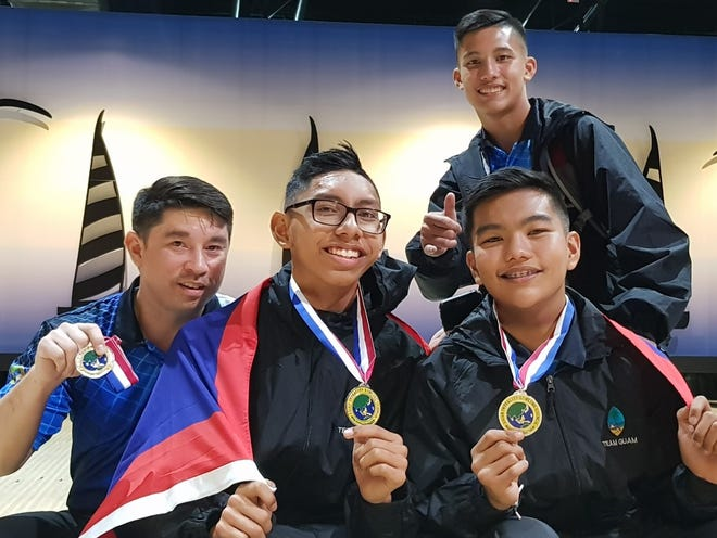 Player/coach Jay Leon Guerrero at left, and Frank Manibusan Jr., congratulate  Noah Taimanglo, left, and Jeremiah Camacho on their Asian Intercity silver-medal performance Nov. 2 in Malaysia.