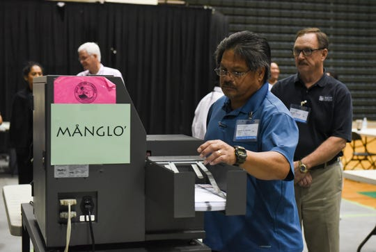 Election worker Ignacio P. Pereda observes sample ballots going through a tabulating machine during a test election at the University of Guam Calvo Field House, Nov. 4, 2018.