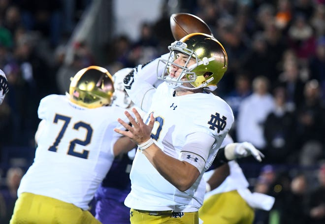 Notre Dame Fighting Irish quarterback Ian Book (12) drop back top pass against the Northwestern Wildcats during the first quarter at Ryan Field.