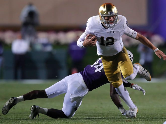 Notre Dame's Ian Book, right, breaks away from a tackle by Northwestern's Montre Hartage during the first half of an NCAA college football game Saturday, Nov. 3, 2018, in Evanston, Ill. (AP Photo/Jim Young)