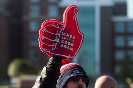 Zech Austin, of Nashville holds up Trump paraphernalia before a Donald Trump rally in support of U.S. Rep. Marsha Blackburn for the U.S. Senate at McKenzie Arena in Chattanooga, Sunday, Nov. 4, 2018.