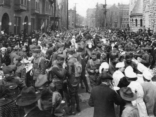Returning World War I soldiers crowd Walnut Street on April 5, 1919. St. John's Cathedral is at right.
