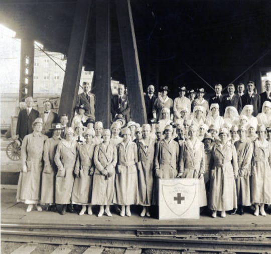 An American Red Cross Canteen group poses for a photo at the Southern Railway tracks near the organization's World War I canteen for soldiers.