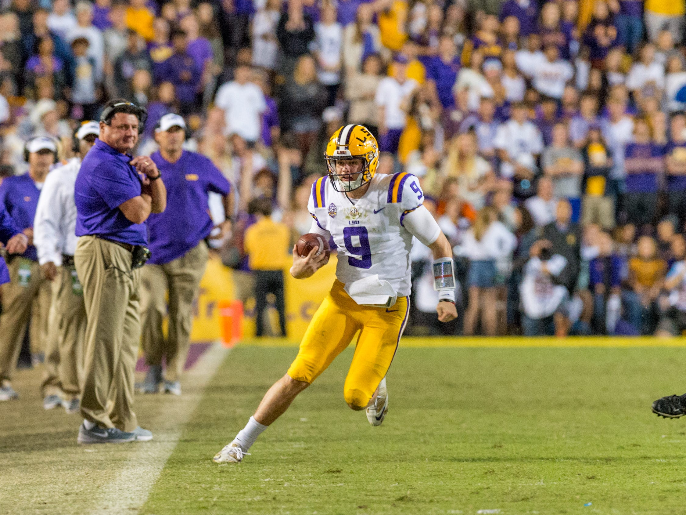 Tigers quarterback is chased out of bounds by lineman Raekwon Davis as The #4 LSU Tigers take on the #1 ranked Alabama Crimson Tide in Tiger Stadium. Saturday, Nov. 3, 2018.