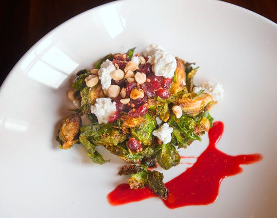 Chef James Moran's crispy Brussels sprouts are quartered and deep fried, then topped with toasted hazelnuts, pickled cranberries and Capriole Farm goat cheese, served with a blood orange black pepper gastrique.