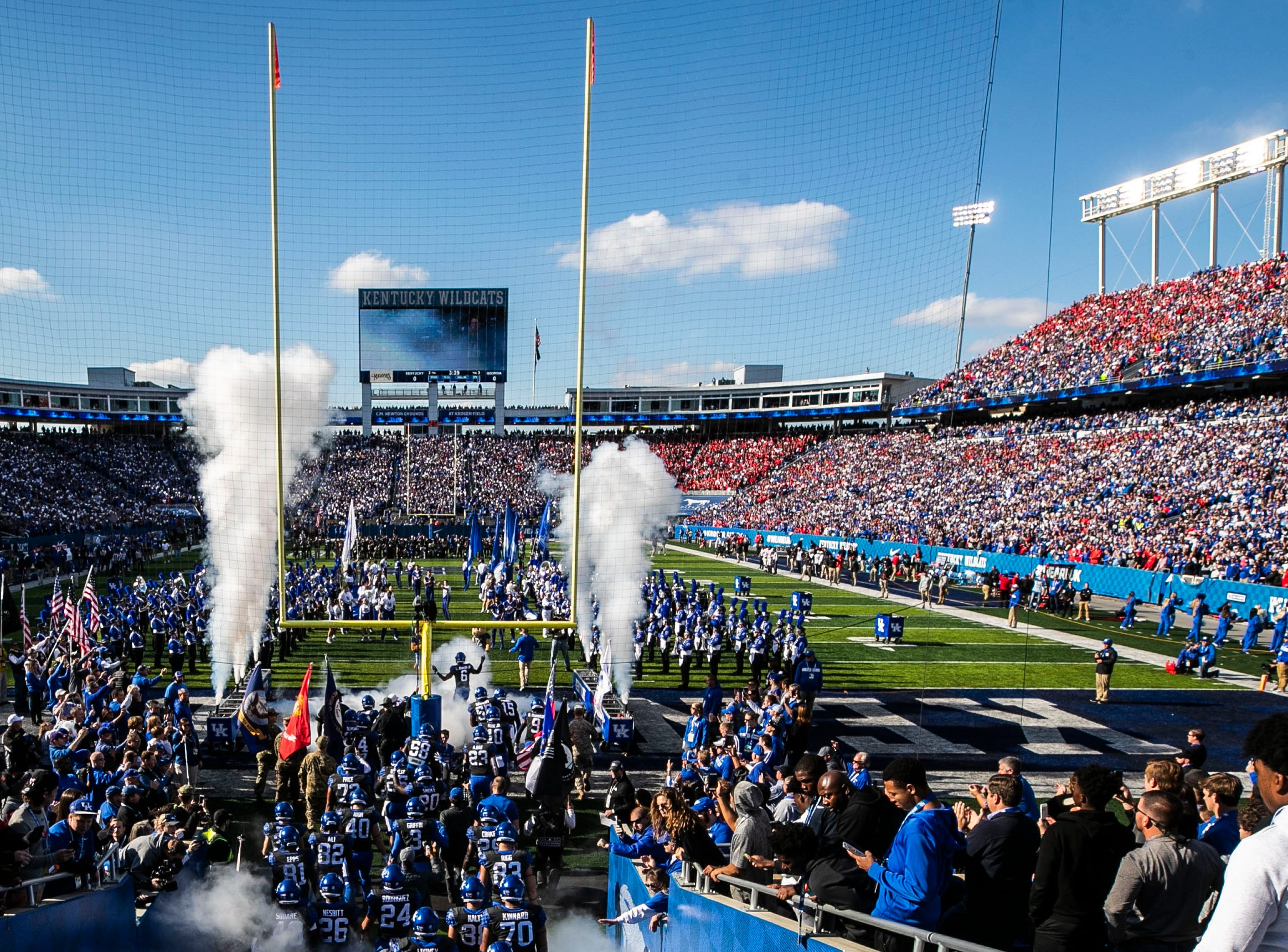 Under smoke and amid the roar of a packed Kroger Field, the Kentucky team runs out on the field before the start against Georgia. Saturday. Nov. 3, 2018