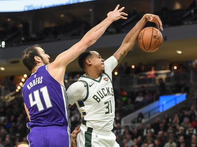 Bucks forward John Henson harvests a rebound against Kings center Kosta Koufos in the third quarter Sunday.