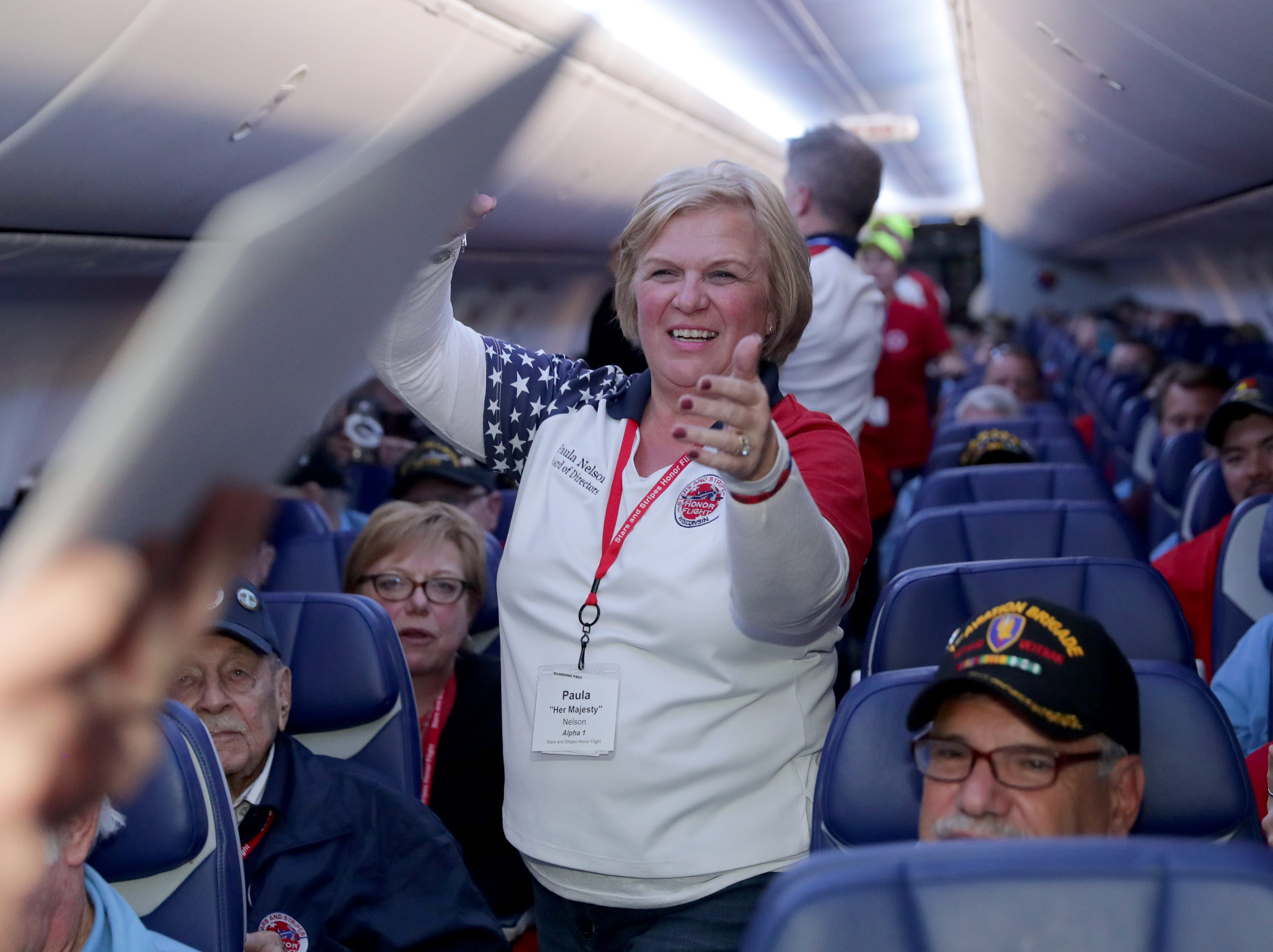 Stars and Stripes Honor Flight President Paula Nelson helps pass out mail during mail call, where veterans are surprised by dozens of letters from loved ones.