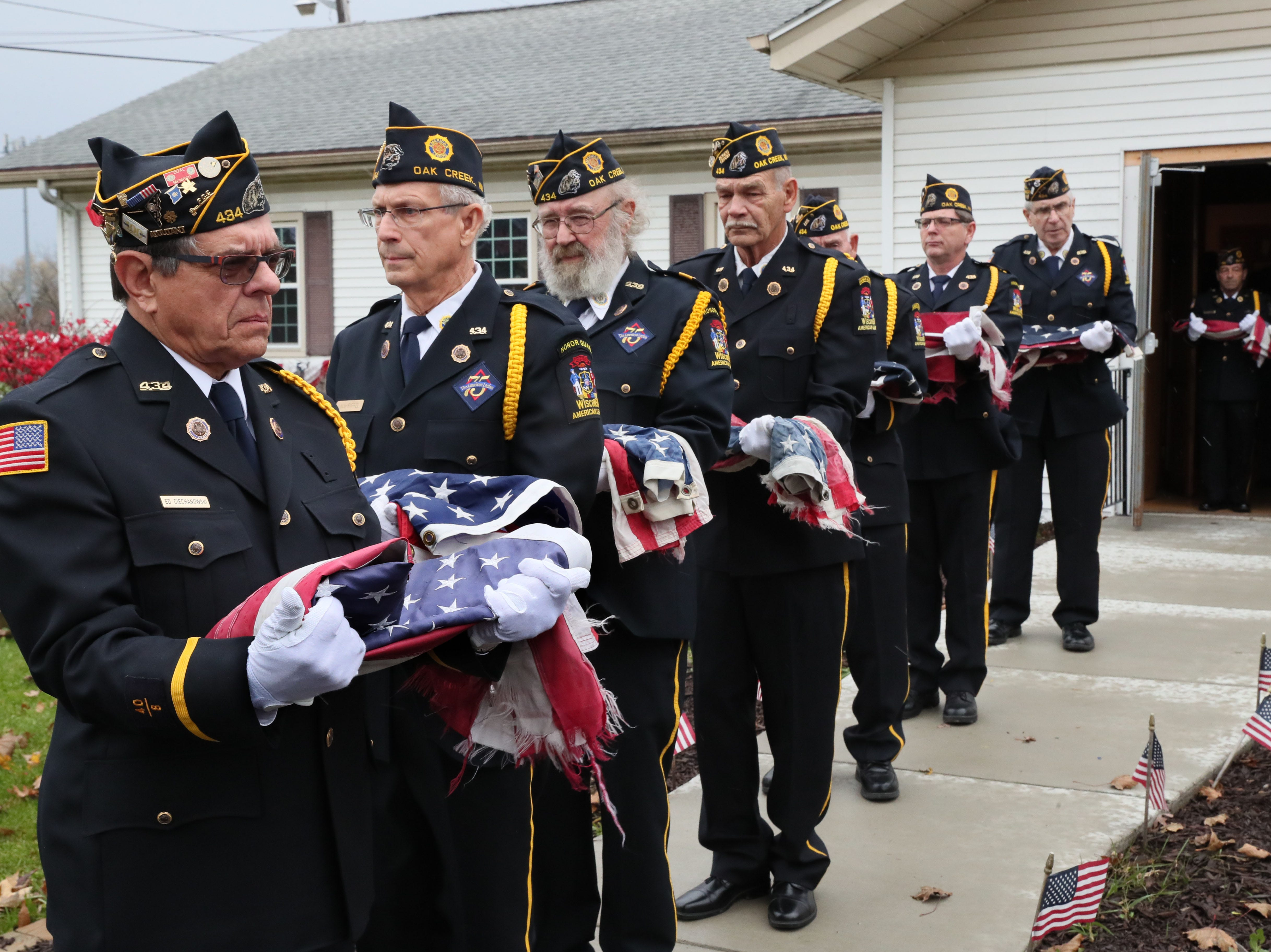 Ed Ciechanowski (far left), a member of the honor guard, holds a flag along with others as they make their way toward a fire where the flags will be destroyed.