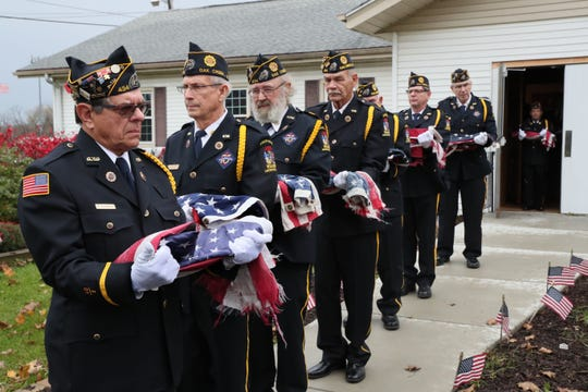 Ed Ciechanowski (far left), a member of the honor guard, holds a flag along with others as they make their way toward a fire where the flags will be retired.