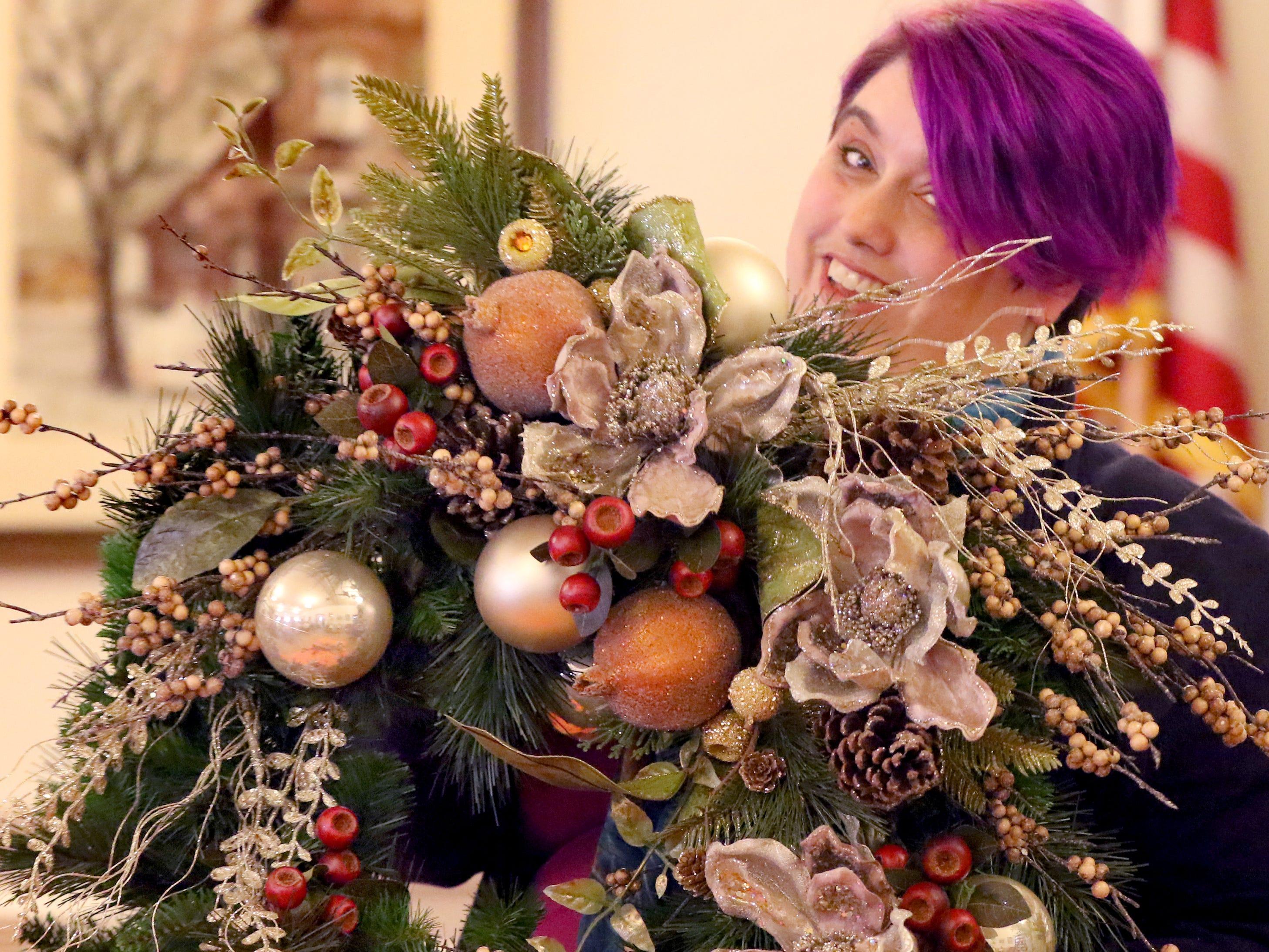 Kimberlee Grob, design manager at Locker's Florist, shows off a wreath she created during a Wauwatosa Woman's Club tea on Nov. 1.