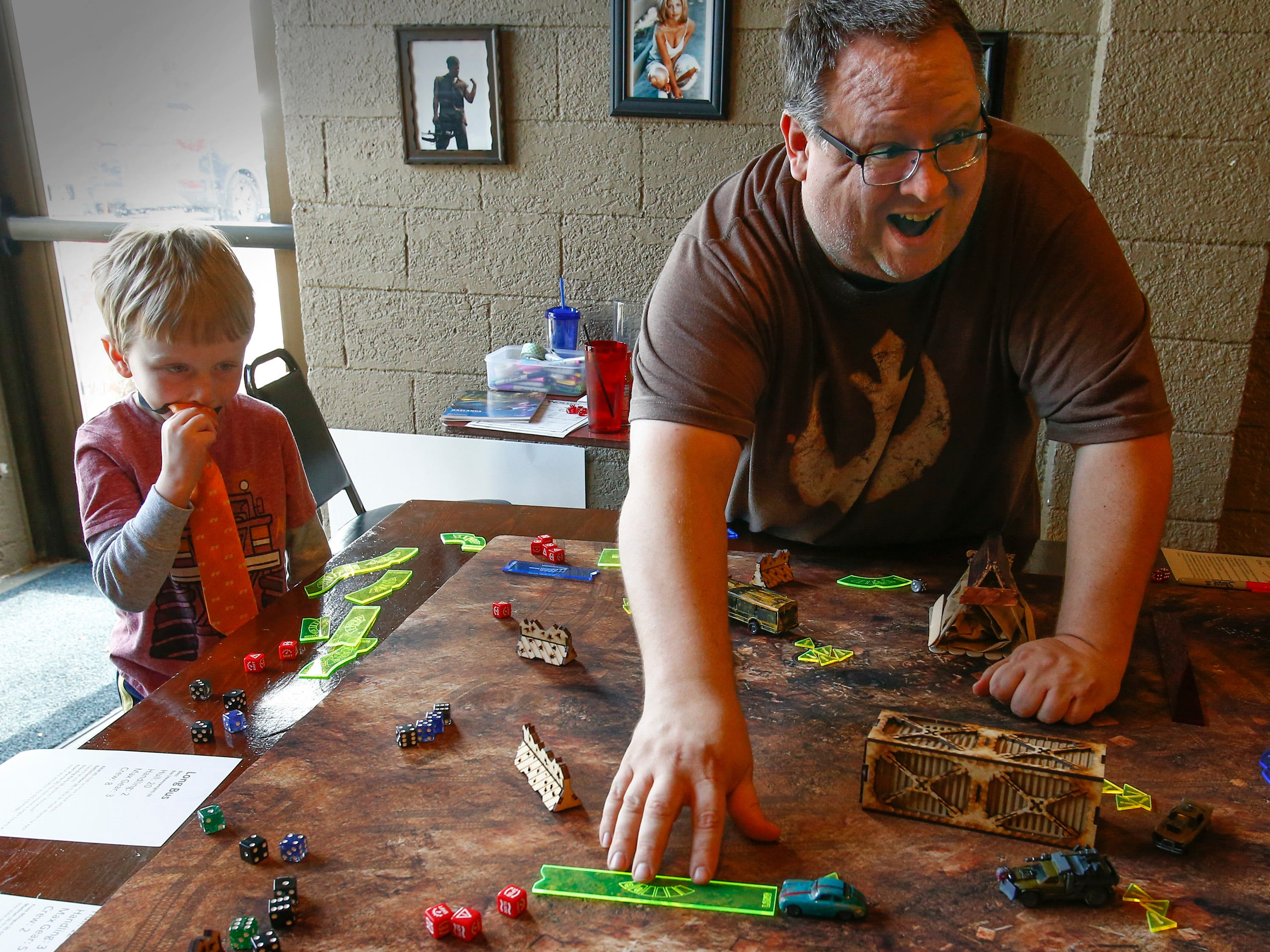 Riley Koemen, 5, of Hales Corners is not to sure about a move by Paul Dworschack-Kinter (right) in a round of the tabletop game Gaslands during a 12-hour Game-A-Thon hosted by FORGE, Feminist Organization for Rebel Geek Empowerment, to benefit Children's Hospital of Wisconsin at 42 Ale House in St. Francis on Nov. 3.