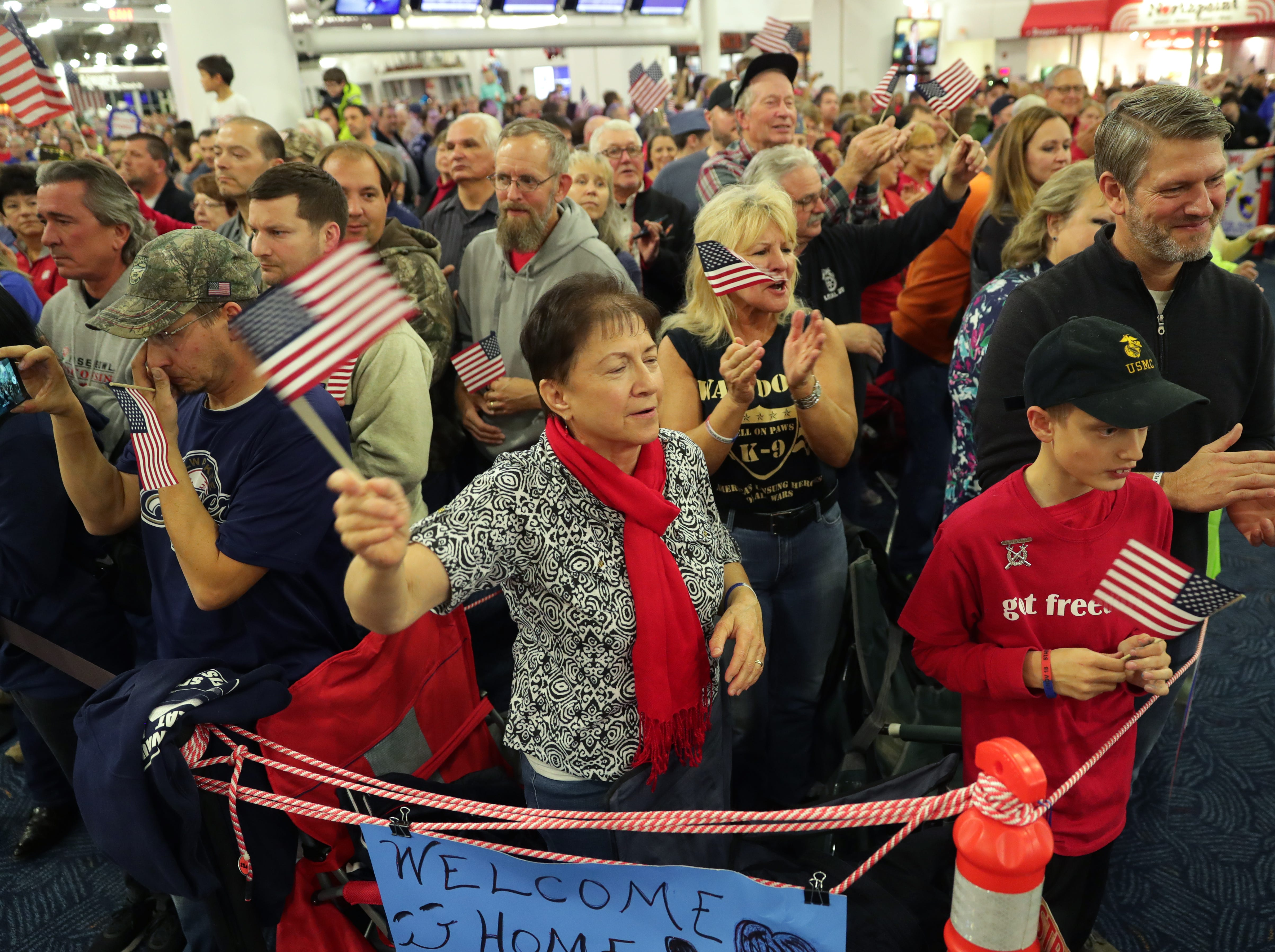 People cheer during the Stars and Stripes Honor Flight welcome home ceremony.