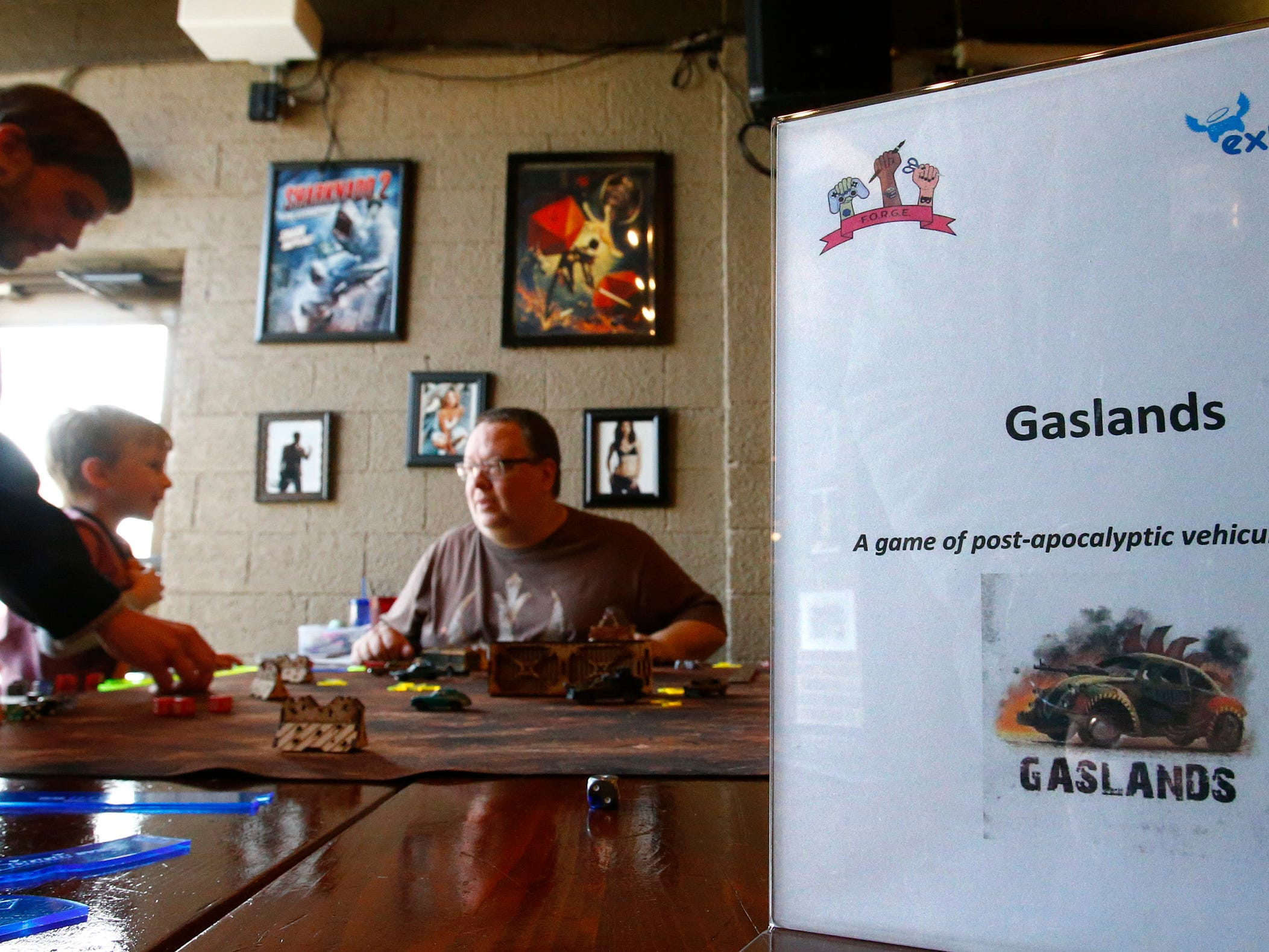 Paul Dworschack-Kinter (right) leads a round of the tabletop game Gaslands during a 12-hour Game-A-Thon hosted by FORGE, Feminist Organization for Rebel Geek Empowerment, to benefit Children's Hospital of Wisconsin at 42 Ale House in St. Francis on Nov. 3.