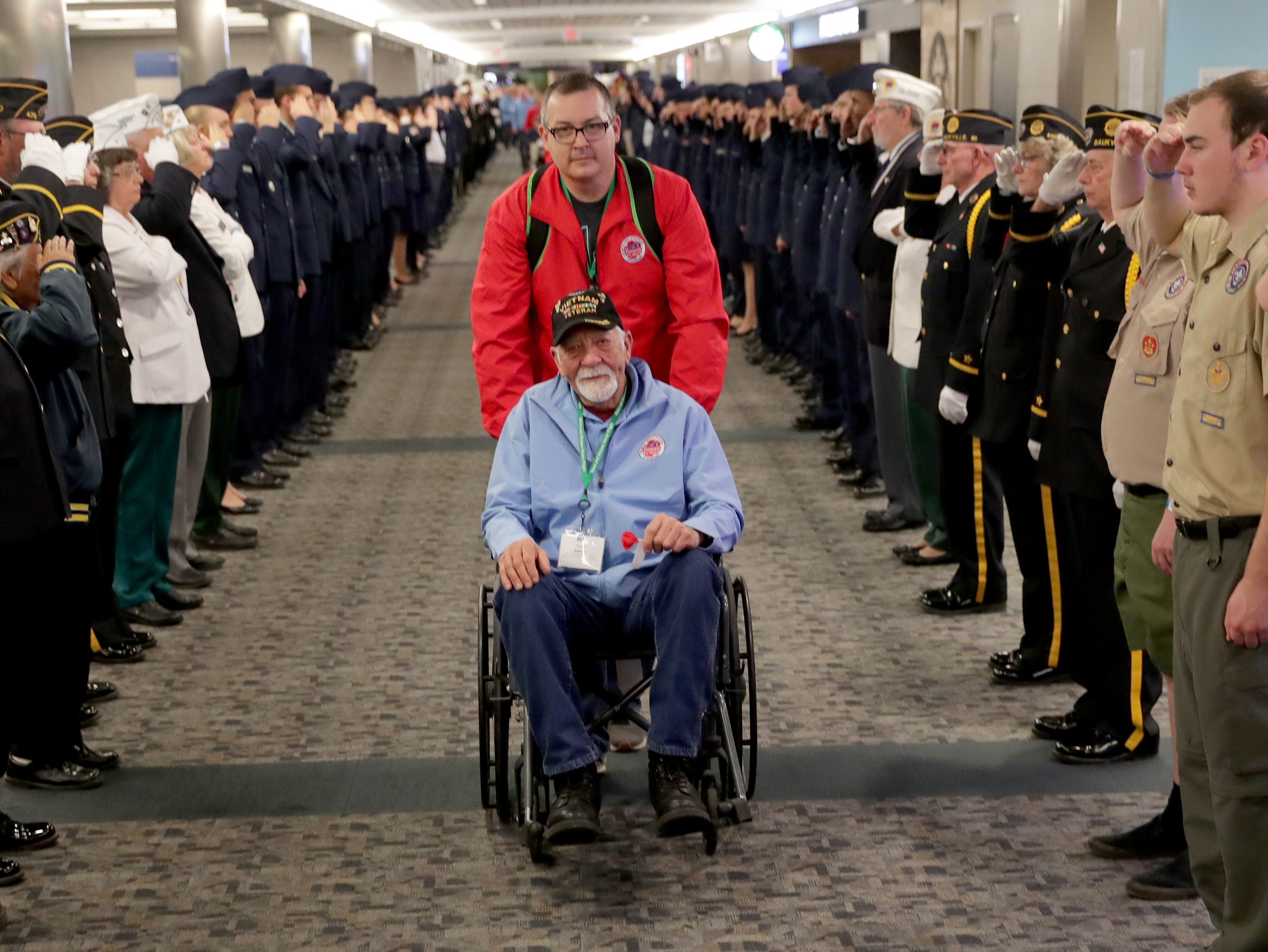 Vietnam Army veteran Bill Grant of West Allis is saluted after getting off the plane with his guardian, Travis Lewein, during the Stars and Stripes Honor Flight welcome home ceremony at Mitchell International Airport in Milwaukee on Saturday.