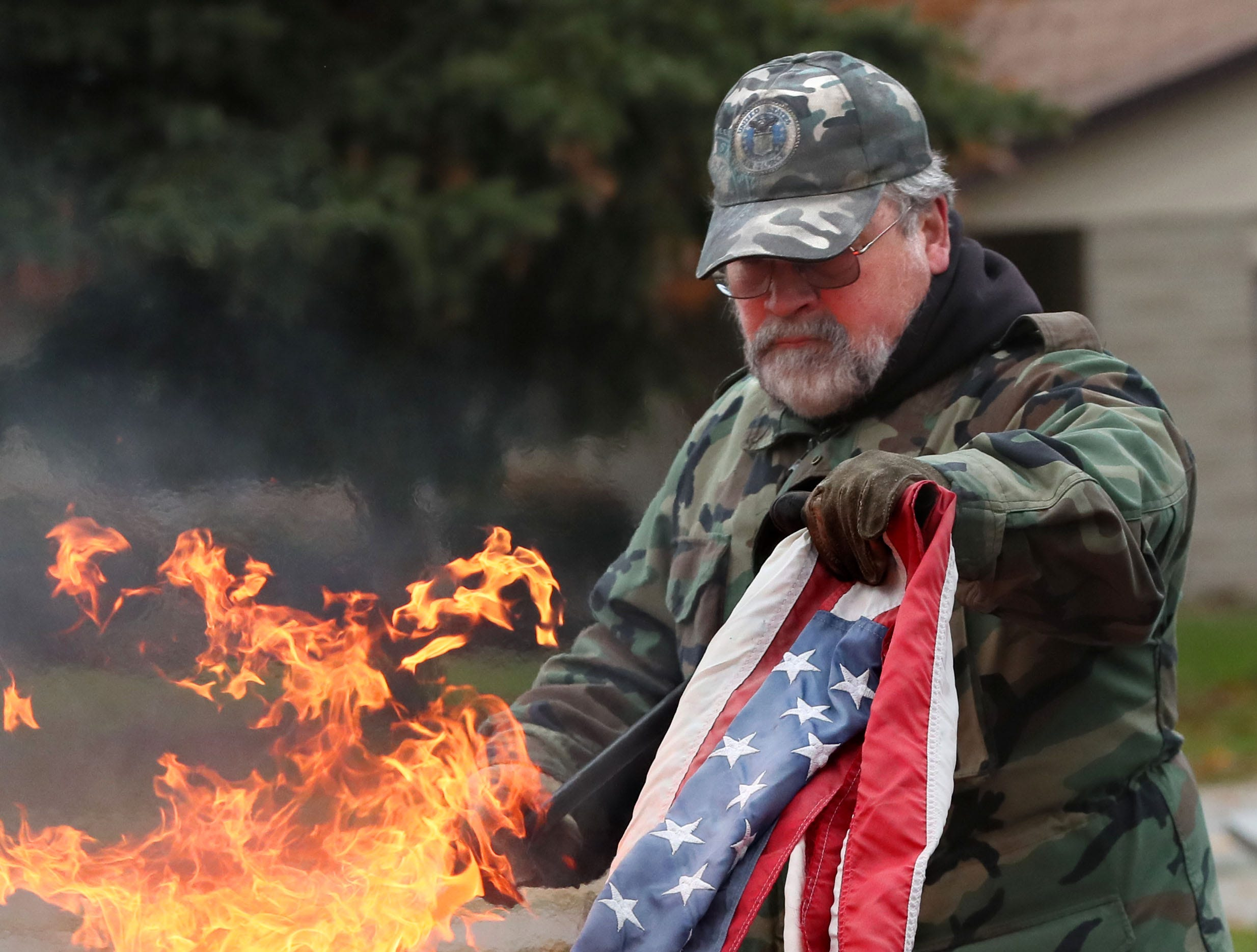 Post member Roger Jenson lowers a flag to be destroyed into the flames.