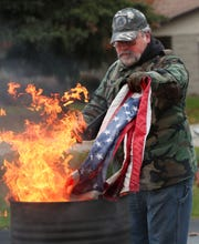 Post member Roger Jenson lowers a flag to be retired into the flames.