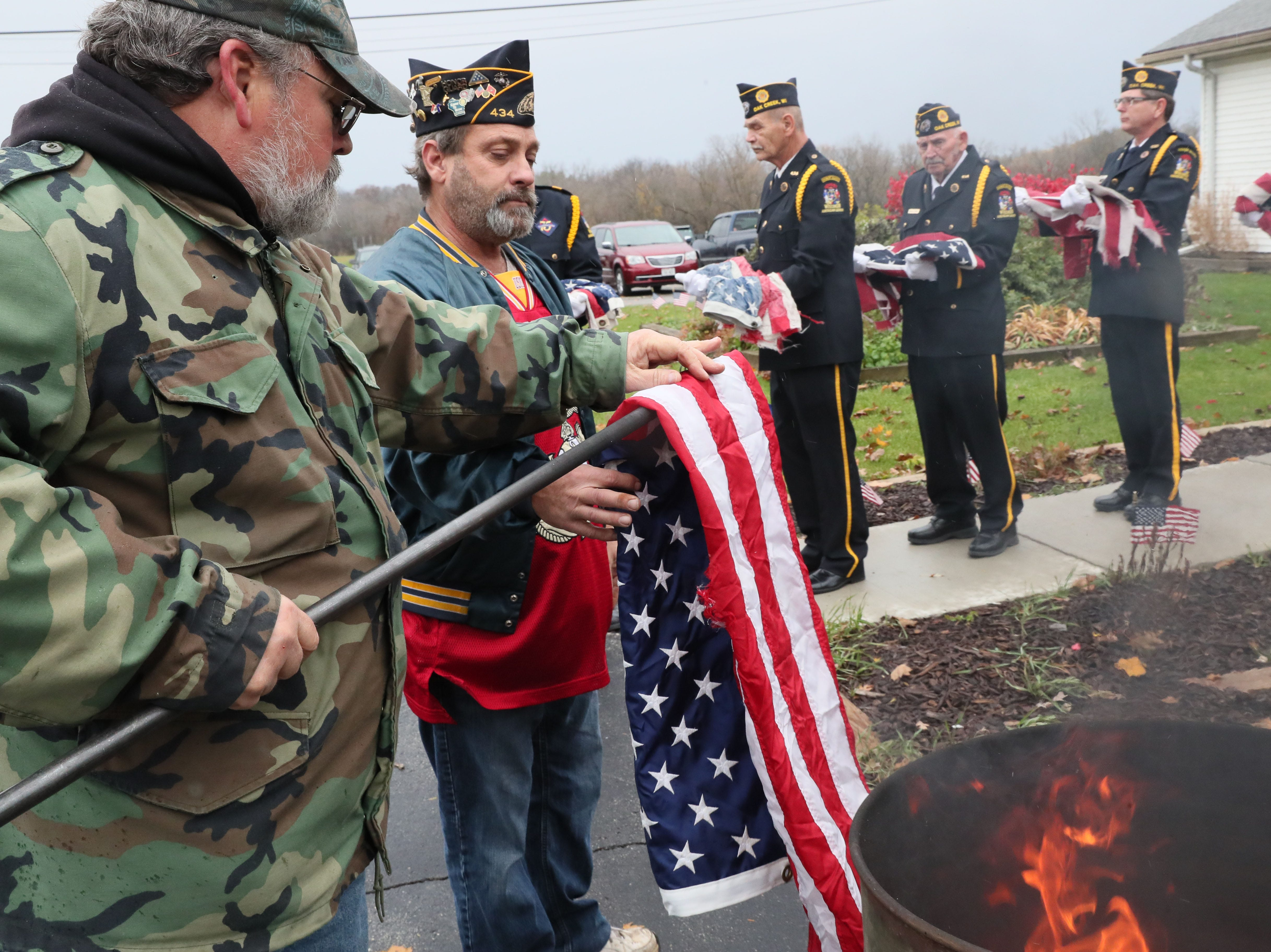 "Roger Jenson (left) takes flags from Second Vice Commander Scott Zalewski (center) to be placed in the burn barrel.  Other members of the honor guard wait at right with flags to be destroyed during a flag retirement ceremony at Oelschlaeger Dallmann American Legion Post 434 in Oak Creek on Sunday. It's an official way that American flags can be ""retired"" and destroyed."