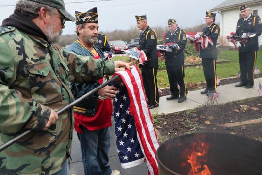 Roger Jenson (left) takes flags from Second Vice Commander Scott Zalewski to be placed in the burn barrel. Other members of the honor guard wait at right with flags to be retired destroyed during a ceremony at Oelschlaeger Dallmann American Legion Post 434 in Oak Creek on Sunday.