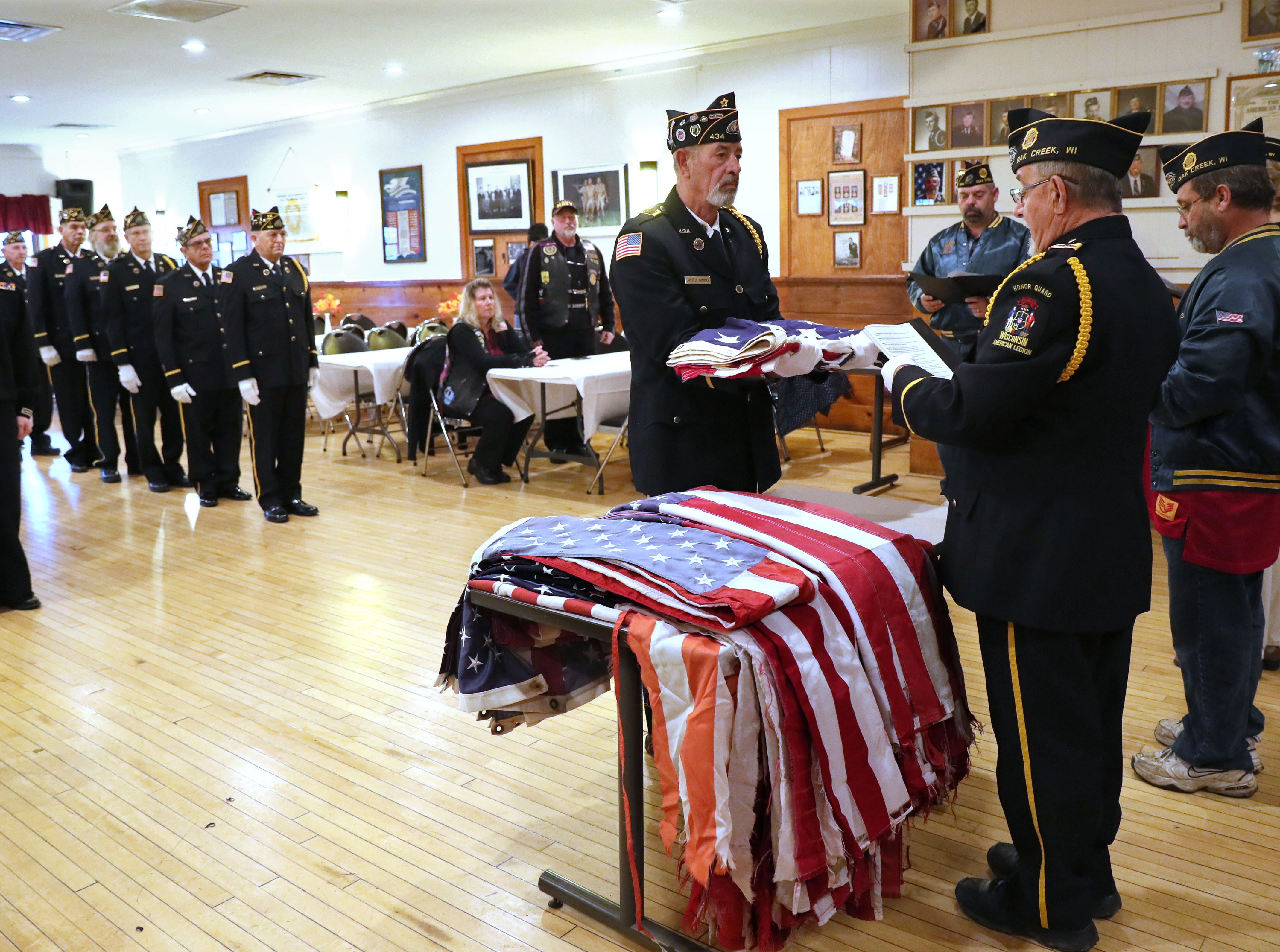 Darrell Wimmer, a member of the honor guard, holds a flag as George Rainer (right), the honor guard commander, starts the ceremony to retire the flags.  Members of the post and a unit of United States Naval Sea Cadets (a high school and middle school program) are in the background.