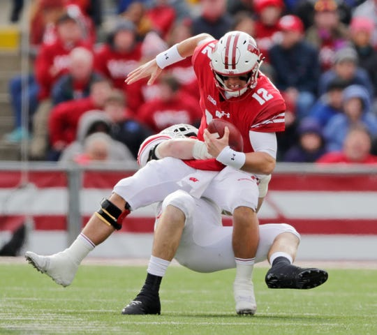 Wisconsin Badgers quarterback Alex Hornibrook (12) is sacked by Rutgers Scarlet Knights defensive lineman Mike Tverdov (97) in the second quarter of a Big Ten football game at Camp Randall Stadium on Saturday, November 3, 2018 in Madison, Wis.