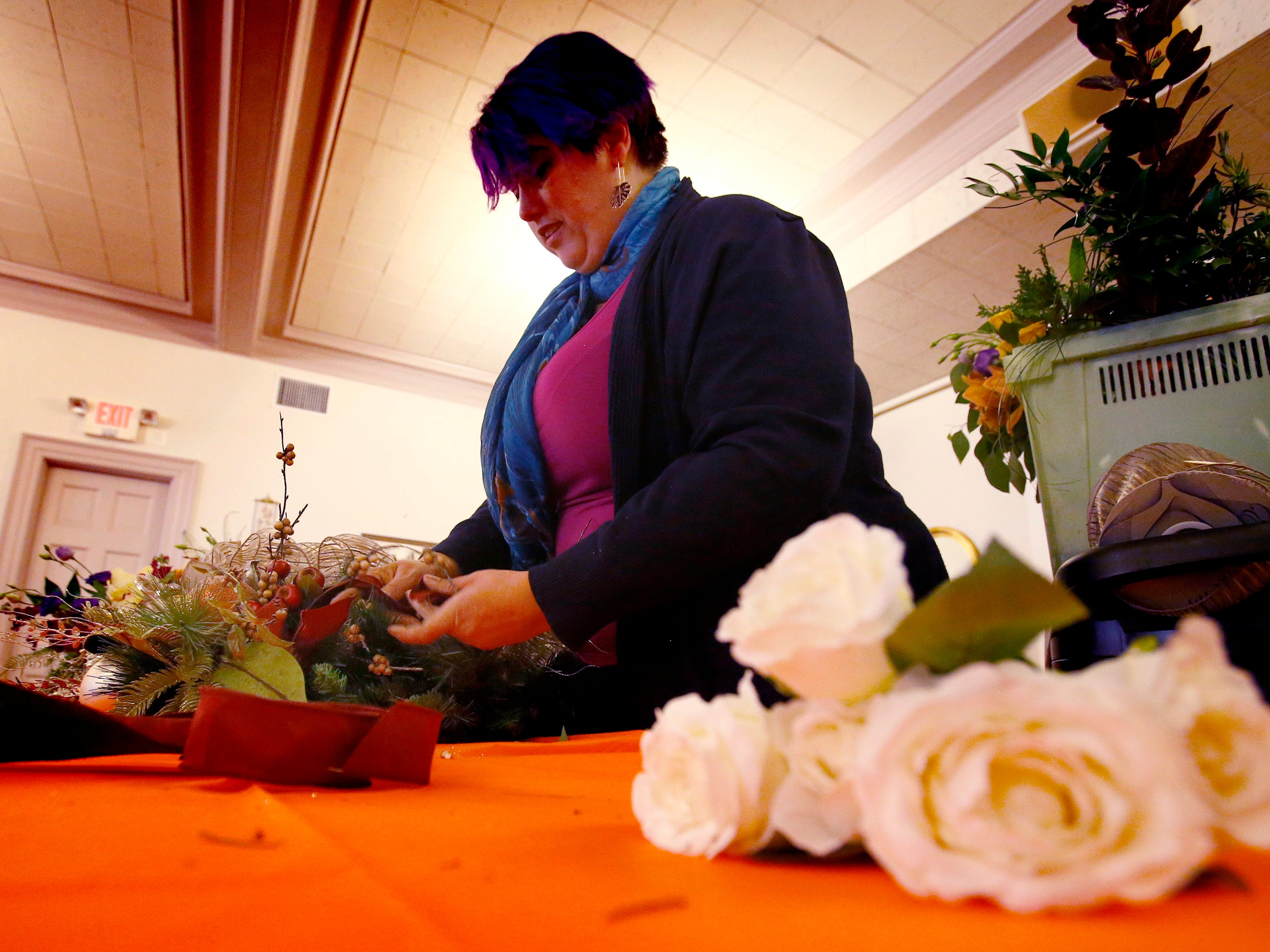 Kimberlee Grob, design manager at Locker's Florist, shows how to make table decor and wreaths during a Wauwatosa Woman's Club tea on Nov. 1.