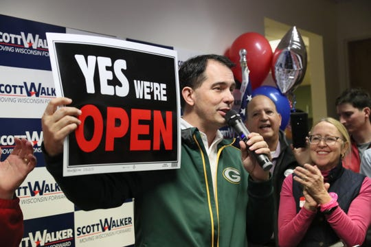 Gov. Scott Walker holds up a sign to tout his record on job creation.