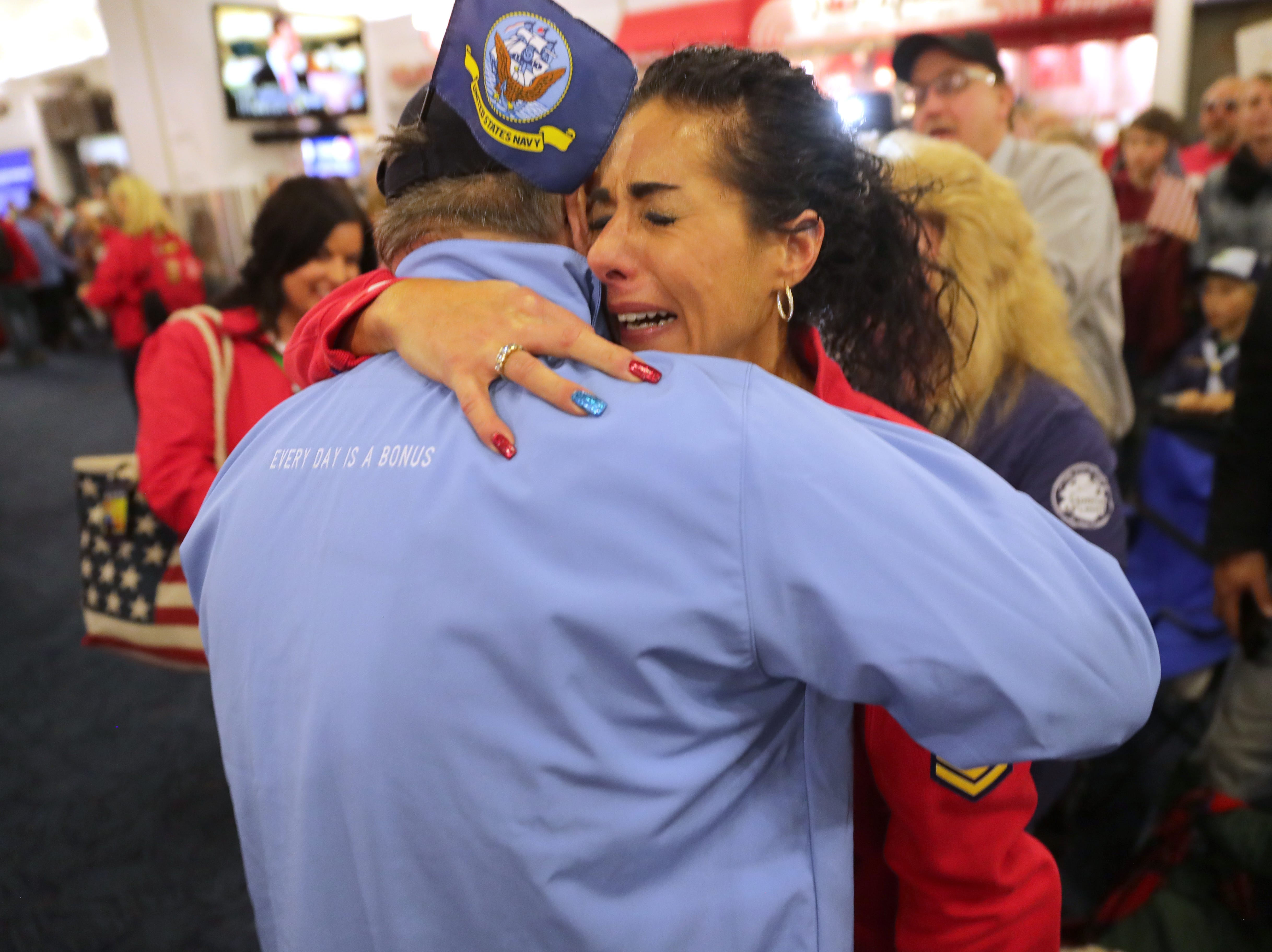 Vietnam Navy veteran Pete Sapienza of Big Bend is hugged by his daughter, Amy Sapienza of Mukwonago, during the Stars and Stripes Honor Flight welcome home ceremony.