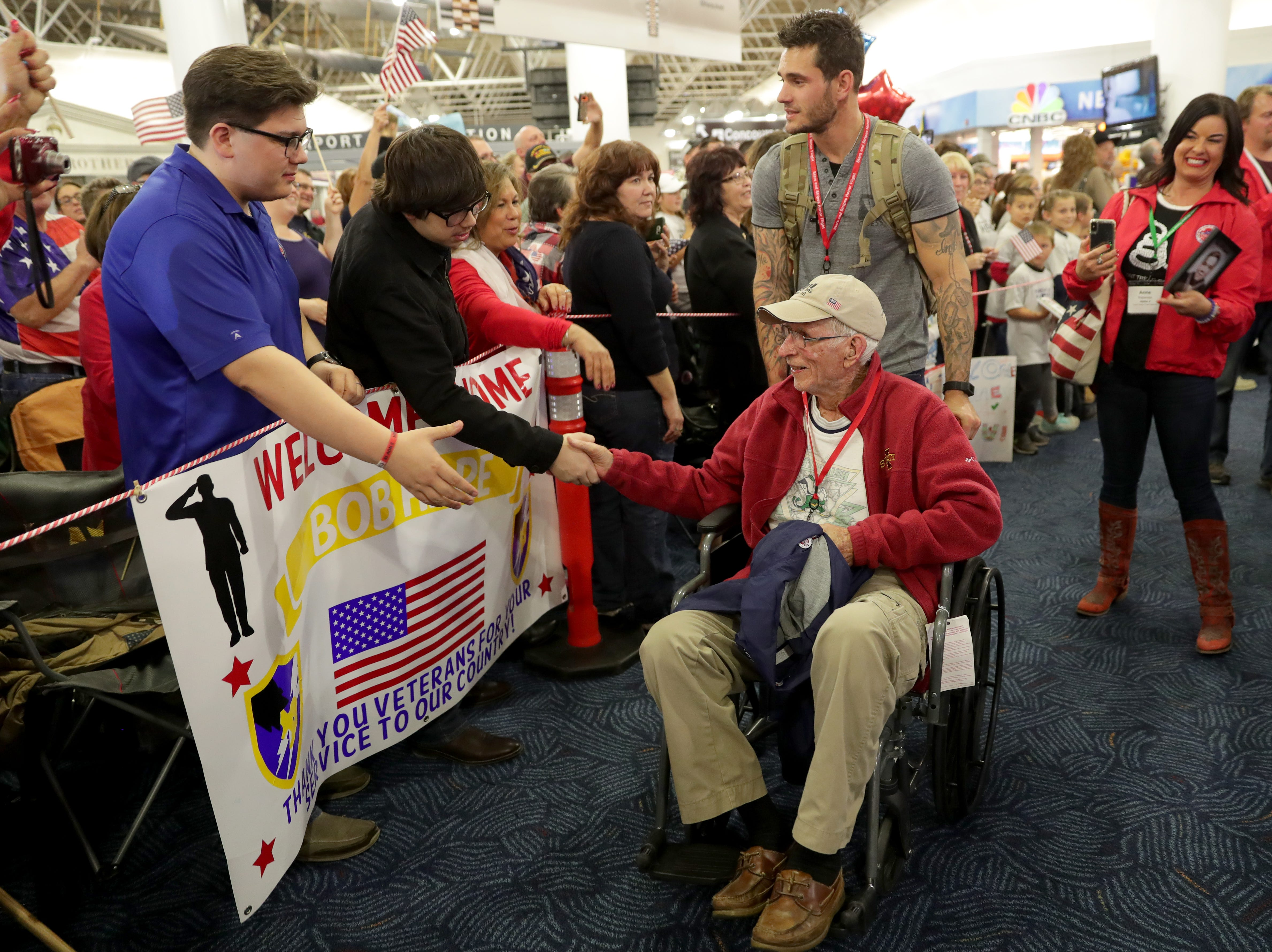 World War II Army veteran Ray Emery, 96, is greeted with his guardian, Emery's grandson, Andrew Rehberg, who served two deployments in Afghanistan, 2010-'11 and 2012-'13, and in Kuwait, 2016-'17, after getting off the plane during the Stars and Stripes Honor Flight welcome home ceremony at Mitchell International Airport in Milwaukee on Saturday.