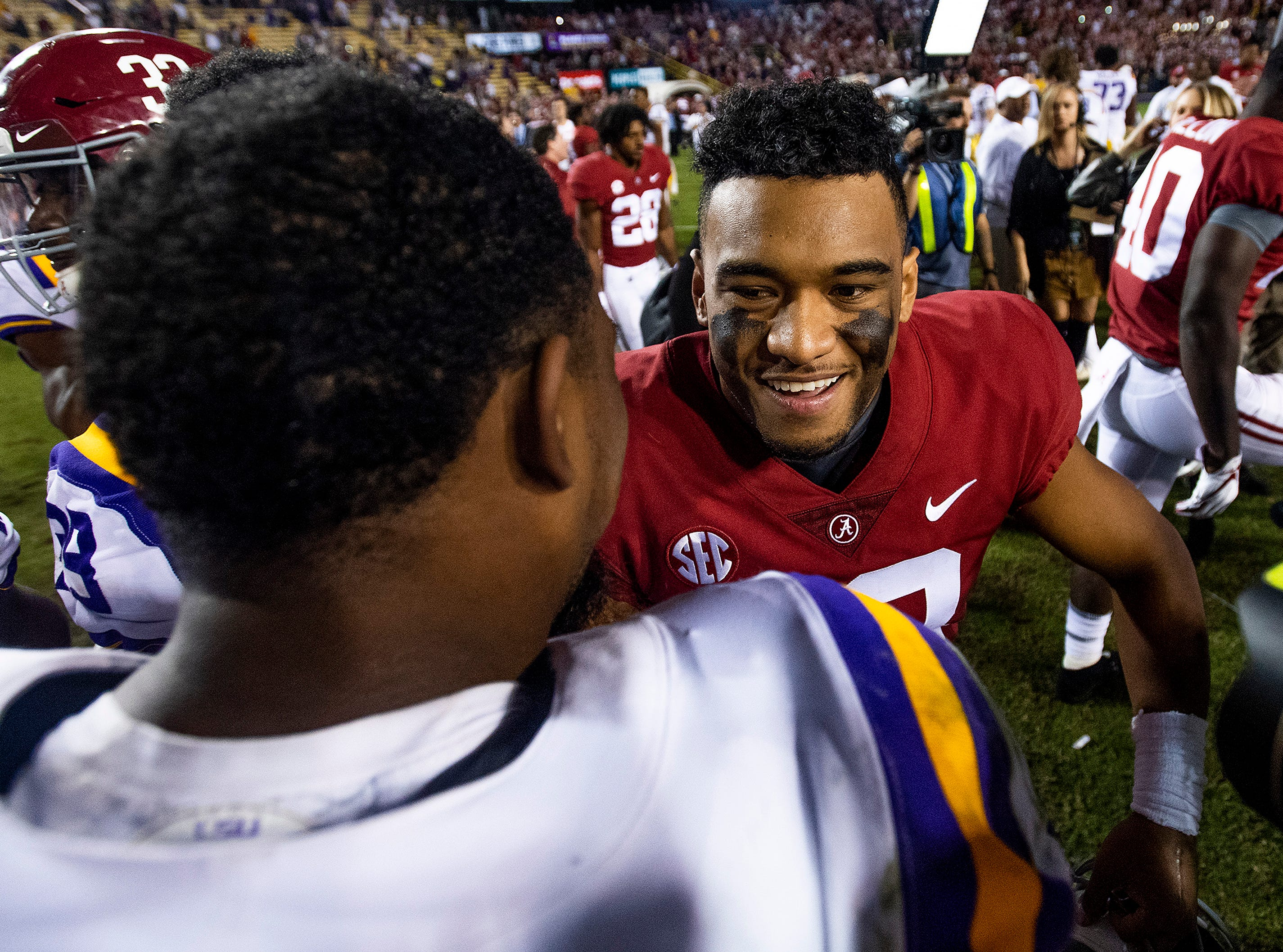 Alabama quarterback Tua Tagovailoa (13) hugs Louisiana State University outside linebacker Michael Divinity, Jr., (45) after defeating LSU at Tiger Stadium in Baton Rouge, La., on Saturday November 3, 2018.