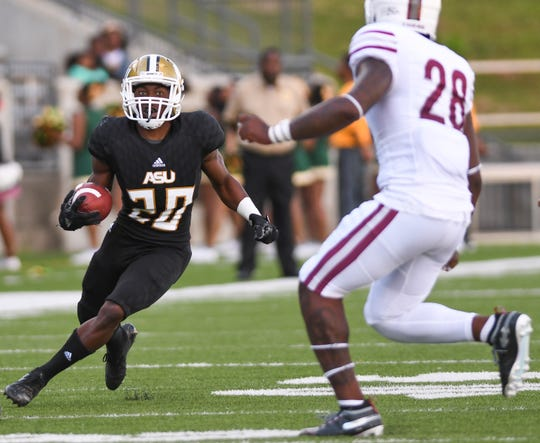 Alabama State running back Ezra Gray (20) dodges Texas Southern linebacker Patrick Howell (28) Saturday, Nov. 3, 2018, at Alabama State University in Montgomery, Ala.
