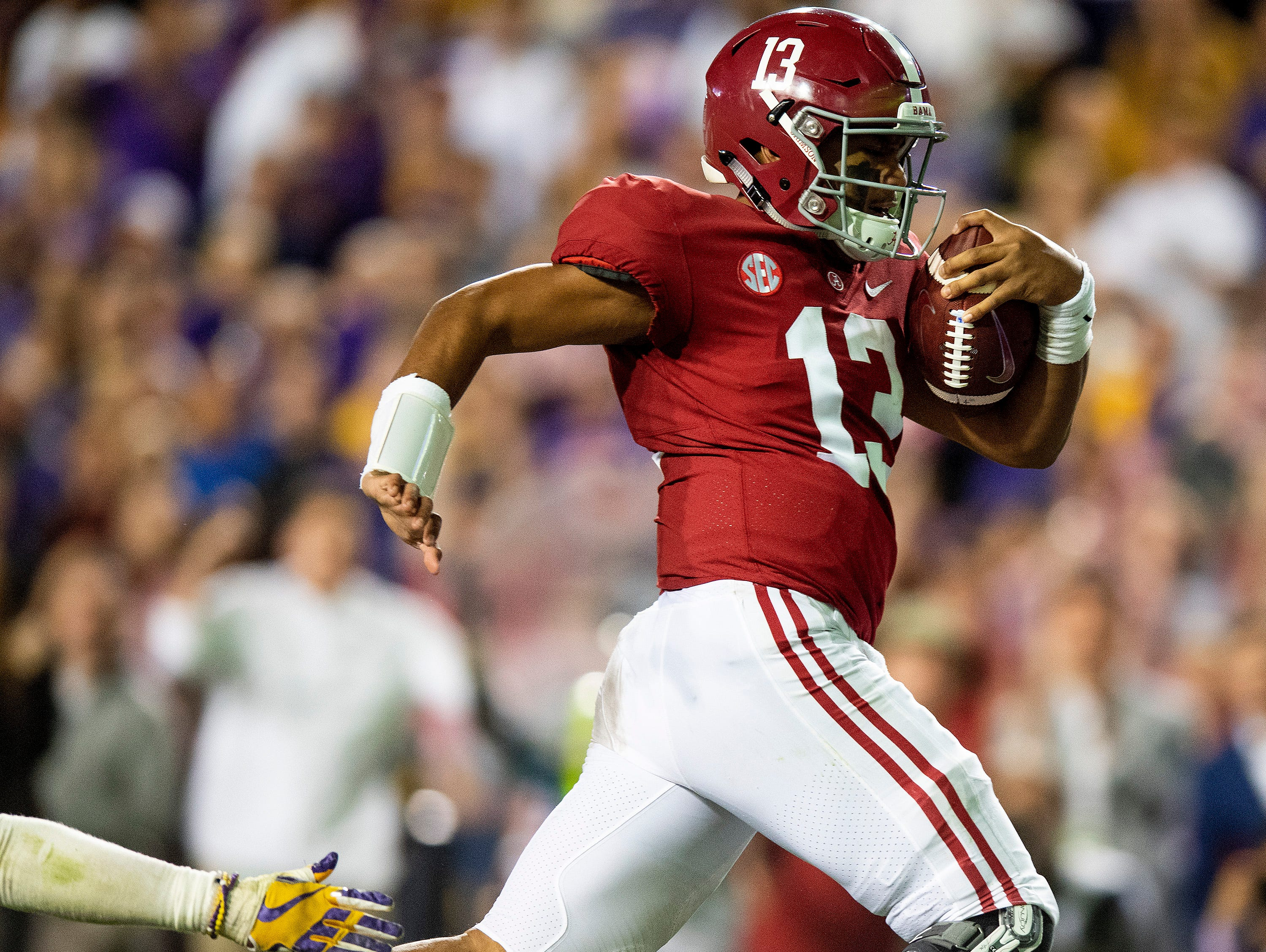 Alabama quarterback Tua Tagovailoa (13) carries for a touchdown against LSU in second half action at Tiger Stadium in Baton Rouge, La., on Saturday November 3, 2018.