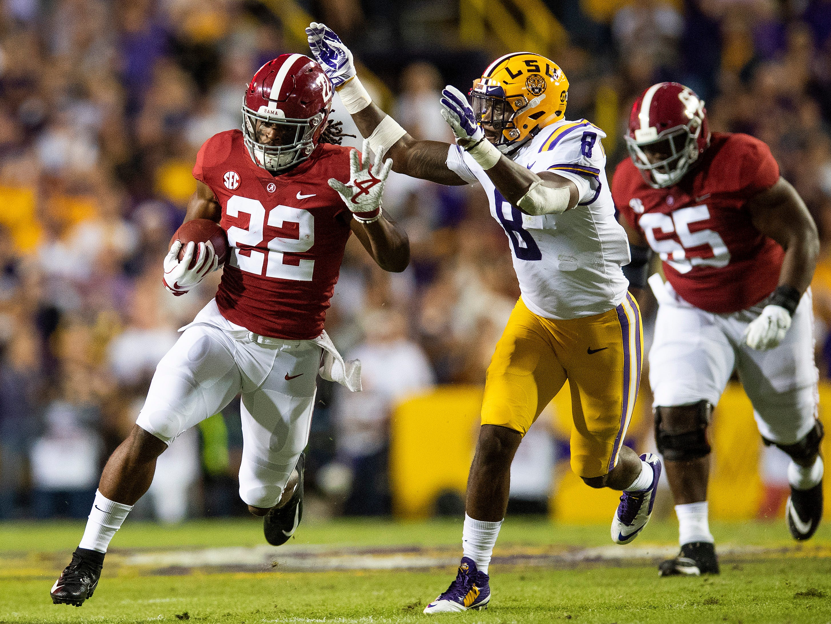 Alabama running back Najee Harris (22) eludes Louisiana State University linebacker Patrick Queen (8) in first half action at Tiger Stadium in Baton Rouge, La., on Saturday November 3, 2018.
