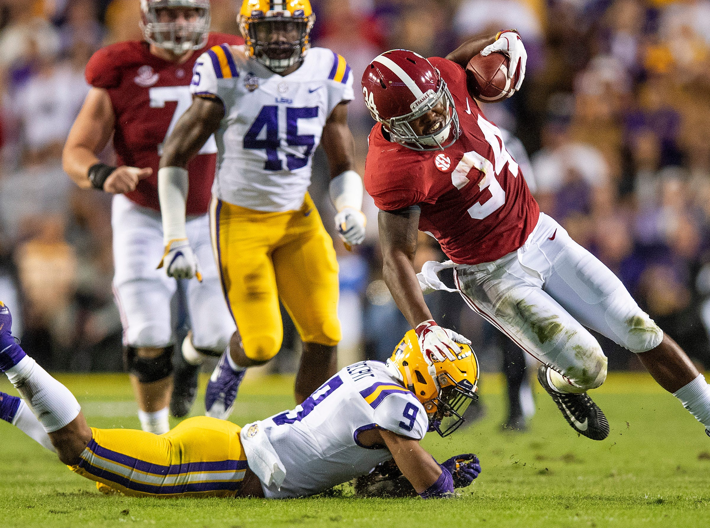 Alabama running back Damien Harris (34) is tripped up by Louisiana State University safety Grant Delpit (9) in first half action at Tiger Stadium in Baton Rouge, La., on Saturday November 3, 2018.