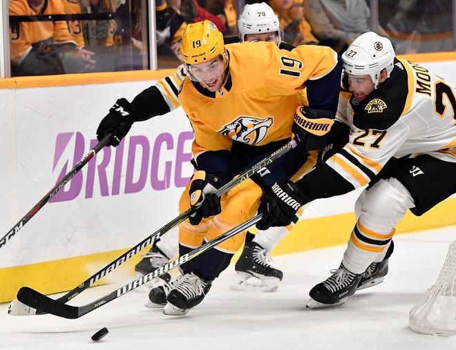 Predators center Calle Jarnkrok (19) takes the puck from Bruins defenseman John Moore (27) during the first period Saturday at Bridgestone Arena.