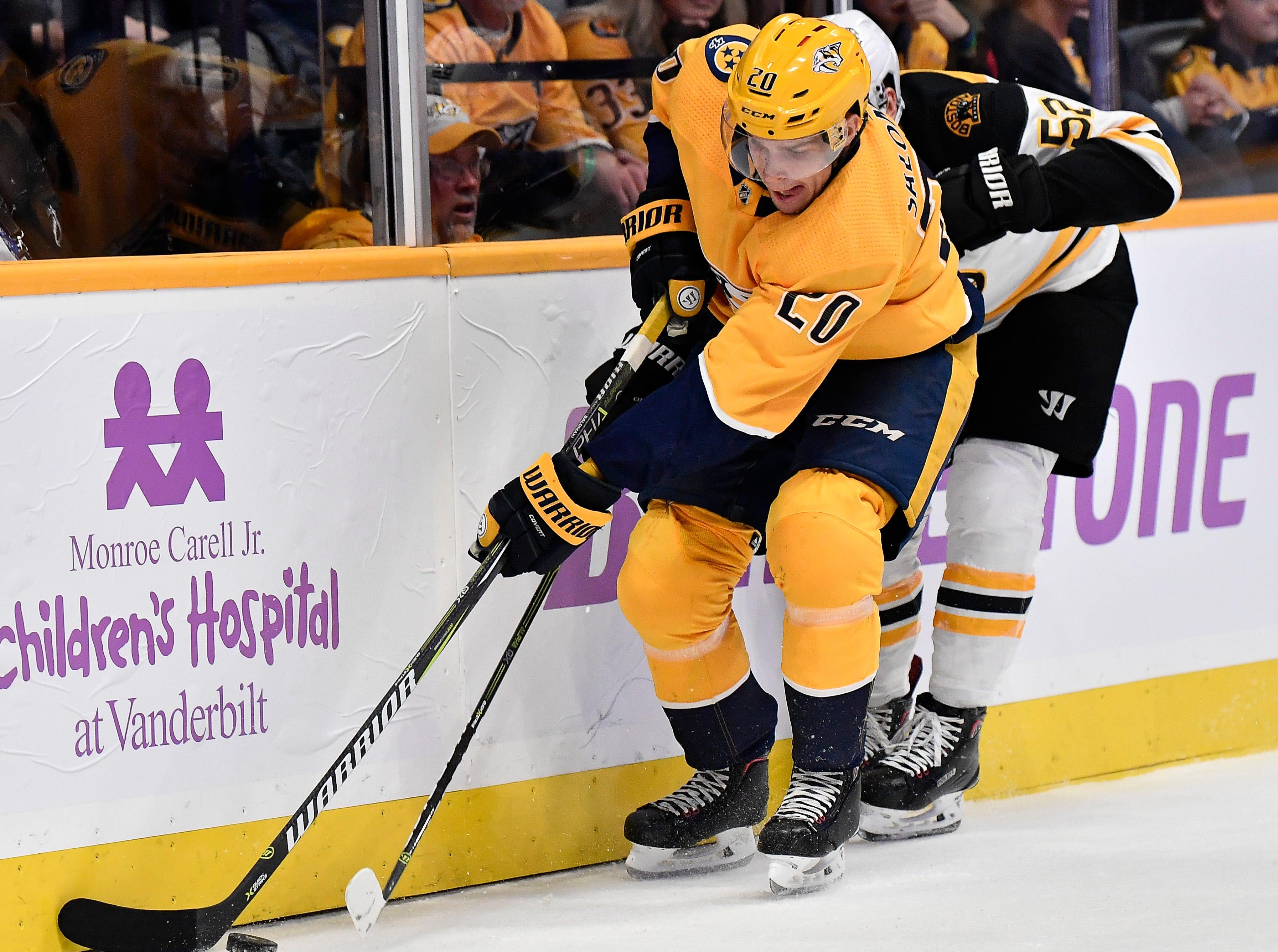 Predators right wing Miikka Salomaki (20) fights for the puck with Bruins center Sean Kuraly (52) during the first period at Bridgestone Arena Saturday, Nov. 3, 2018, in Nashville, Tenn.