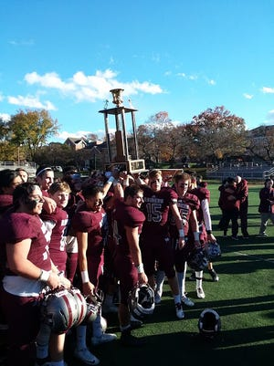 Nutley football players holding the Mayor's Trophy, which goes to the winner of the annual football game with Belleville.