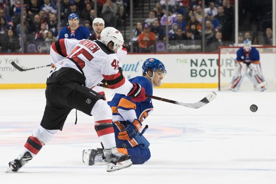 New Jersey Devils defenseman Sami Vatanen (45) and New York Islanders left wing Anders Lee chase the puck during the second period of an NHL hockey game, Saturday, Nov. 3, 2018, in New York. (