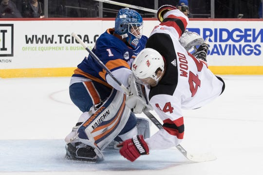 New Jersey Devils left wing Miles Wood (44) flips over New York Islanders goaltender Thomas Greiss (1) during the first period of an NHL hockey game, Saturday, Nov. 3, 2018, in New York.