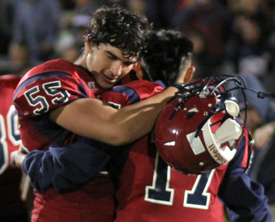 Juniors Justin Morgan (55) and Julio Moran (17) embrace following a 49-35 Wildcat victory over Silver High Friday night.